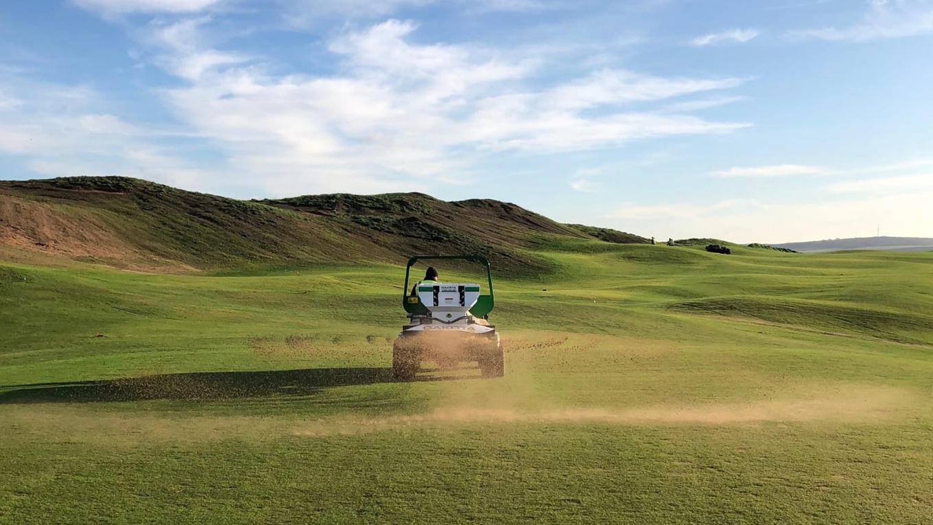 A ProGator with spreader at work during the new course's grow-in phase.